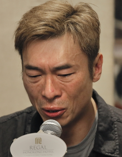 Hong Kong singer Andy Hui reacts at the press conference in Hong Kong, Tuesday, April 16, 2019. Hong Kong's Apple Daily newspaper published video that purported to show Andy Hui being intimate in a taxi with another Hong actress, decades younger than him, Jacqueline Wong. (AP Photo/Vincent Yu)