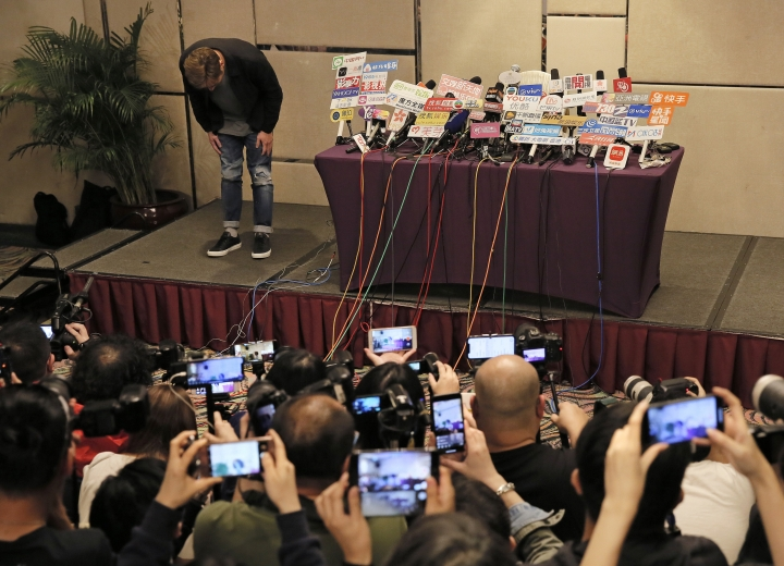 Hong Kong singer Andy Hui bows before a press conference about his affair in Hong Kong, Tuesday, April 16, 2019. Hong Kong's Apple Daily newspaper published video that purported to show Andy Hui being intimate in a taxi with another Hong actress, decades younger than him, Jacqueline Wong. (AP Photo/Vincent Yu)