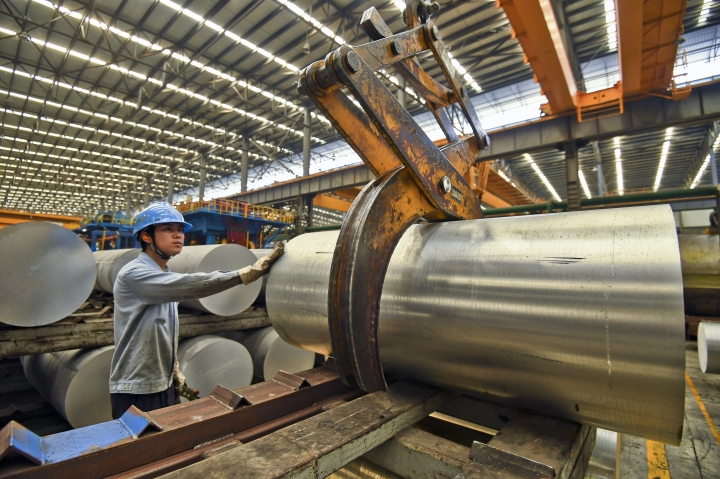 In this Wednesday, April 10, 2019, photo, a worker transfers an aluminium product at a factory in Nanning in south China's Guangxi Zhuang Autonomous Region. China's economic growth held steady in the latest quarter despite a tariff war with Washington, suggesting Beijing's efforts to reverse a slowdown might be gaining traction. (Chinatopix via AP)