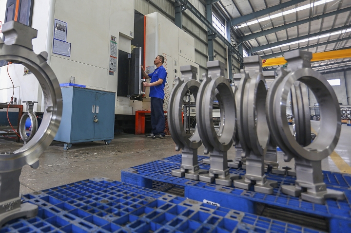 In this Wednesday, April 10, 2019, photo, a worker handles a machine producing valve at a factory in Jinjiang city in southeast China's Fujian province. China's economic growth held steady in the latest quarter despite a tariff war with Washington, suggesting Beijing's efforts to reverse a slowdown might be gaining traction. (Chinatopix via AP)