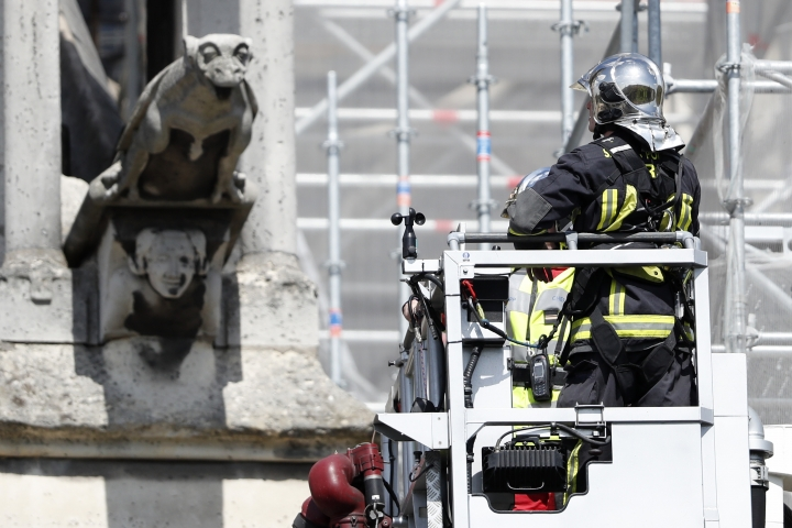 "A firefighter watches a preserved gargoyle of Notre Dame cathedral Wednesday, April 17, 2019 in Paris. Notre Dame Cathedral would have been completely burned to the ground in a ""chain reaction collapse"" had firefighters not moved rapidly in deploying their equipment to battle the blaze racing through the landmark monument, a Paris official said Wednesday. (AP Photo/Thibault Camus)"