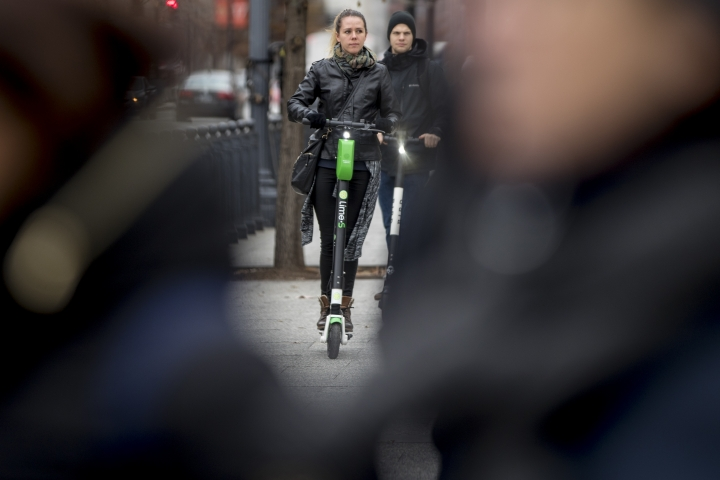 In this Dec. 4, 2018, photo a couple rides scooters near the White House in Washington. Electric scooters are overtaking station-based bicycles as the most popular form of shared transportation outside transit and cars. (AP Photo/Andrew Harnik)