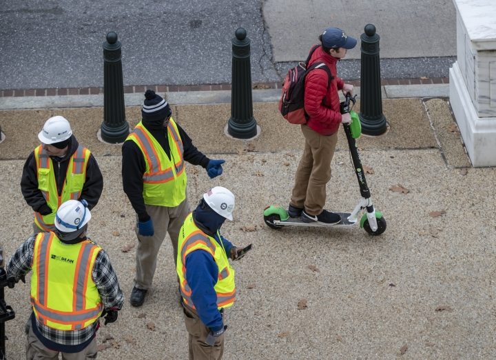 In this Dec. 5, 2018, photo a rider maneuvers a Lime brand electric scooter on a sidewalk past workers on Capitol Hill in Washington. Electric scooters are overtaking station-based bicycles as the most popular form of shared transportation outside transit and cars. (AP Photo/J. Scott Applewhite)