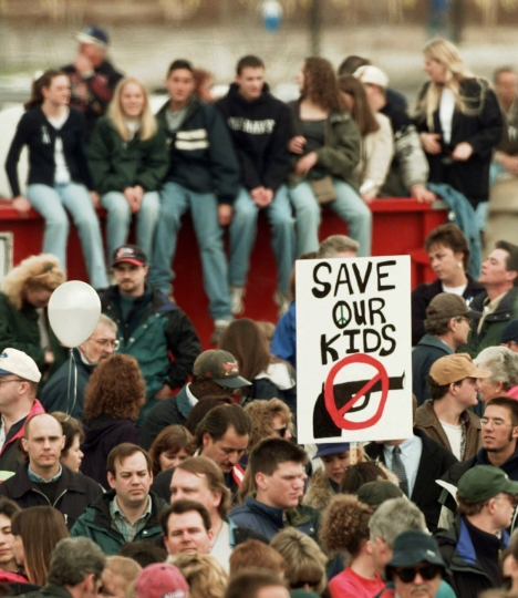 """FILE - In this April 25, 1999, file photo, a participant at a memorial service for the victims of the Columbine High School shooting rampage holds a """"NO GUNS"""" sign in Littleton, Colo. Data shows that such shootings are less frequent and with fewer killed than in the years that preceded Columbine. Still, Americans worry about how safe schools are. (AP Photo/Eric Gay, File)"""