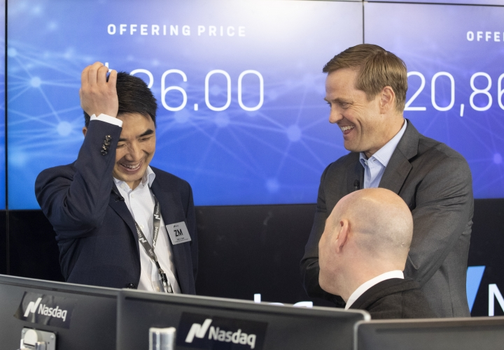 Zoom CEO Eric Yuan, left, talks with Nasdaq's Executive Vice President Nelson Griggs, standing right, and Jay Heller, head of Nasdaq's IPO Execution Team, prior to the opening price for Zoom, Thursday, April 18, 2019, in New York. The videoconferencing company is headquartered in San Jose, Calif. (AP Photo/Mark Lennihan)