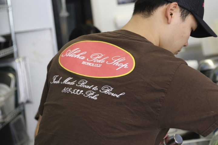 "This Tuesday, April 16, 2019, photo shows Ryne Aniya preparing food before the lunch rush at Aloha Poke Shop, a store in Honolulu that received a letter from Chicago-based Aloha Poke Co. saying the Illinois company had trademarked ""Aloha Poke"" and the Hawaii company would need to change its name. Hawaii lawmakers are considering adopting a resolution calling for the creation of legal protections for Native Hawaiian cultural intellectual property. (AP Photo/Audrey McAvoy)"