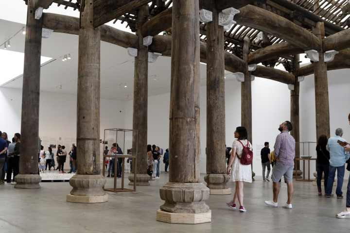 """People walk through a piece titled """"Ancestral Hall of the Wang Family,"""" part of an ancient Chinese construction rescued by Chinese concept artist and government critic Ai Weiwei, at the Contemporary Art University Museum (MUAC ) in Mexico City, Mexico, Saturday, April 13, 2019. The piece creates a striking contrast between the remote memory of his country and the recent memory of Mexico, at the exhibit titled """"Reestablish Memories."""" (AP Photo/Claudio Cruz)"""
