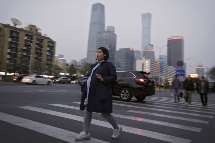 In this Wednesday, April 17, 2019, photo, a pregnant woman walks across a road near the Central Business District during the evening rush hour in Beijing. Remarks by the head of Chinese online business giant Alibaba, Ma Jack, one of China's richest men, that young people should work 12-hour days, six days a week if they want financial success have prompted a public debate over work-life balance in the country. Online complaints included blaming long work hours for a lower birth rate in the country. (AP Photo/Andy Wong)