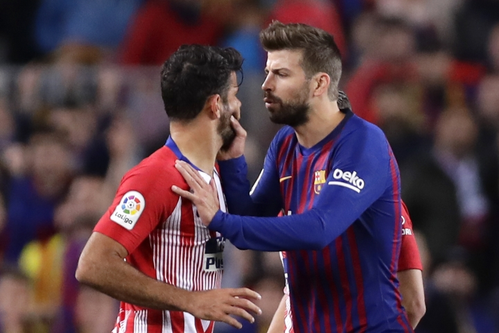 Barcelona's Gerard Pique, right, talks to Atletico forward Diego Costa as he tries to calm him after he was sent off with a red card for insulting referee Jesus Gil Manzano during a Spanish La Liga soccer match between FC Barcelona and Atletico Madrid at the Camp Nou stadium in Barcelona, Spain, Saturday April 6, 2019. (AP Photo/Manu Fernandez)