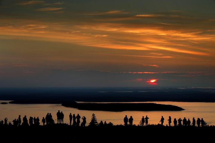 FILE-In this July 31, 2018 file photo, a crowd of early-risers gather near the summit of Cadillac Mountain in Acadia National Park to be among the first in the continental United States to see the sunrise, near Bar Harbor, Maine. The town of Bar Harbor plans to begin charging to park next month. The move comes amid ever-increasing seasonal traffic to Bar Harbor and Acadia National Park, which set a visitation record in 2018.(AP Photo/Robert F. Bukaty, file)