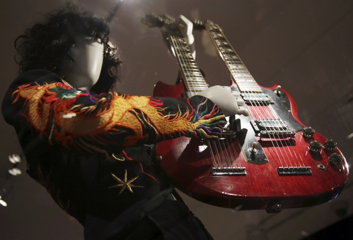 """This April 1, 2019 file photo shows a double-neck guitar played by Jimmy Page of Led Zeppelin displayed at the exhibit """"Play It Loud: Instruments of Rock & Roll,"""" at the Metropolitan Museum of Art in New York. The exhibit, which showcases the instruments of rock and roll legends, runs until Oct. 1, 2019. (AP Photo/Seth Wenig, File)"""