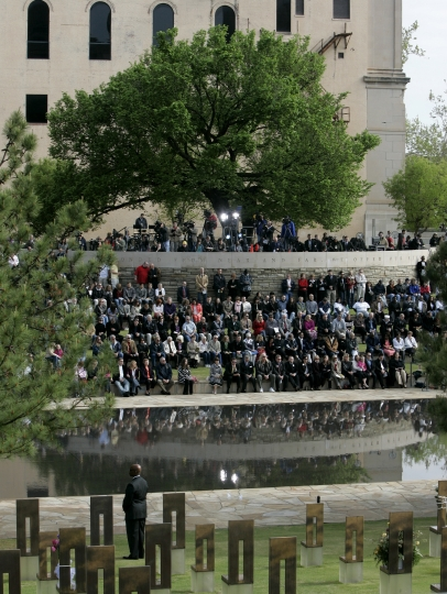 FILE - In this April 19, 2010 file photo, people gather under the Survivor Tree at the Oklahoma City National Memorial during a ceremony marking the 15th anniversary of the Oklahoma City bombing. As part of the city's annual day of remembrance Friday, April 19, 2019 – the 24th anniversary of the attack – civic leaders will plant a tree in a city park that was cloned from this scarred American elm that survived the deadliest act of domestic terrorism on U.S. soil. (AP Photo/Sue Ogrocki, File)