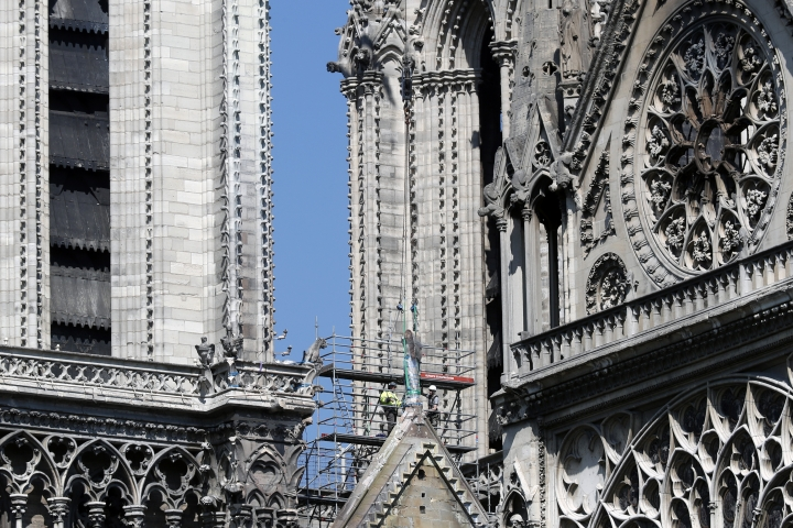 Workers prepare to remove a statue from the damaged Notre Dame cathedral, in Paris, Friday, April 19, 2019. Rebuilding Notre Dame, the 800-year-old Paris cathedral devastated by fire this week, will cost billions of dollars as architects, historians and artisans work to preserve the medieval landmark. (AP Photo/Thibault Camus)