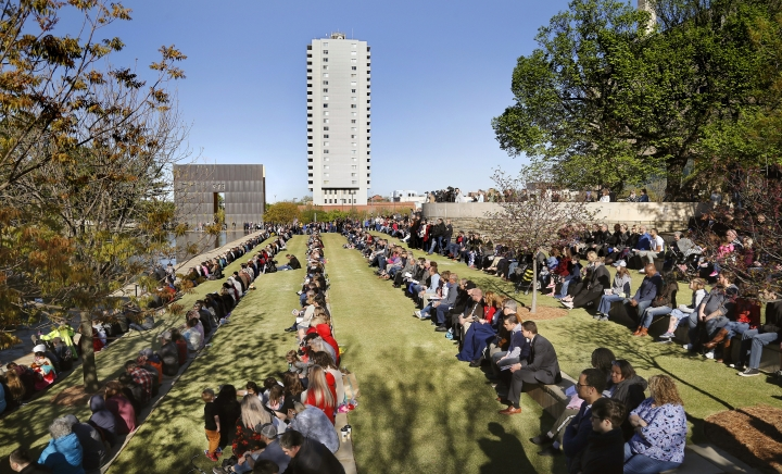 Visitors and guests fill the stone benches on the north side of the Reflecting Pool at the 24th Anniversary Remembrance Ceremony at the Oklahoma City National Memorial & Museum on Friday, April 19, 2019. At right is the Survivor Tree, an American elm tree more than 90 years old that stood at ground zero when the bomb exploded. It was given its name because it survived the bomb's blast. The event honors the memory of the 168 people killed on April 19, 1995, during a terrorist attack on the Alfred P. Murrah Federal Building in downtown Oklahoma City. (Jim Beckel/The Oklahoman via AP)