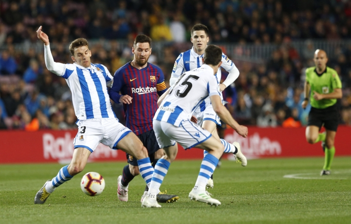 Barcelona forward Lionel Messi fights for the ball against Real Sociedad's Diego Llorente, left and Aritz Elustondo during a Spanish La Liga soccer match between FC Barcelona and Real Sociedad at the Camp Nou stadium in Barcelona, Spain, Saturday, April 20, 2019. (AP Photo/Joan Monfort)