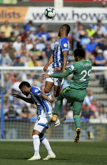 Huddersfiled Town's Steve Mounie and Watford's Etienne Capoue contest a header during the English Premier League soccer match between Huddersfield and Watford at the John Smith's stadium, Huddersfield, England. Saturday, April 20, 2019. (Clint Hughes/PA via AP)