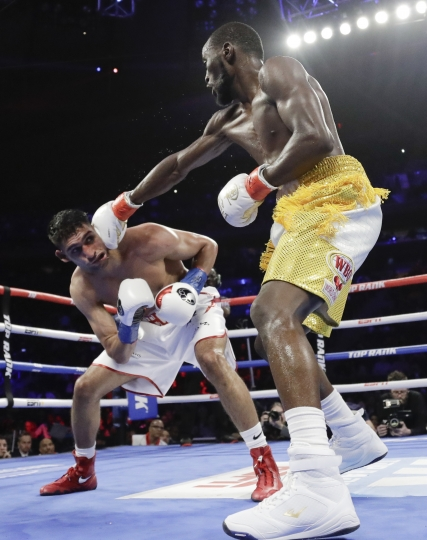 Terence Crawford, right, punches England's Amir Khan during the fifth round of a WBO world welterweight championship boxing match Sunday, April 21, 2019, in New York. Crawford won the fight when Kahn could no longer continue after a low blow in the sixth round. (AP Photo/Frank Franklin II)