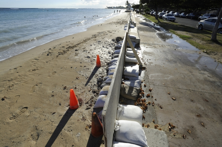 In this June 23, 2017 photo, sand bags line the beach at Ala Moana Beach Park in Honolulu as record high tides hit the islands. Some of Hawaii's most iconic beaches could soon be underwater as rising sea levels caused by global warming overtake its white sand beaches and bustling city streets. That's alarming for a state where beach tourism is the primary economic driver. (Honolulu Star-Advertiser, Bruce Asato via AP)