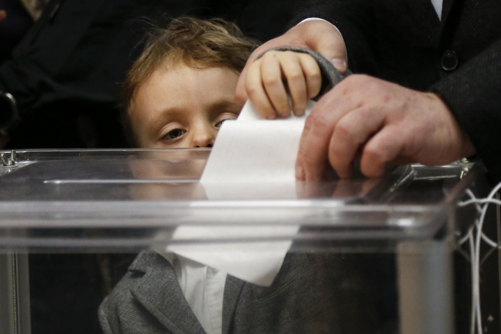 Ukrainian President Petro Poroshenko casts his ballot as his grandson Petro, looks at the ballot at a polling station, during the second round of presidential elections in Kiev, Ukraine, Sunday, April 21, 2019. Top issues in the election have been corruption, the economy and how to end the conflict with Russia-backed rebels in eastern Ukraine. (AP Photo/Efrem Lukatsky)