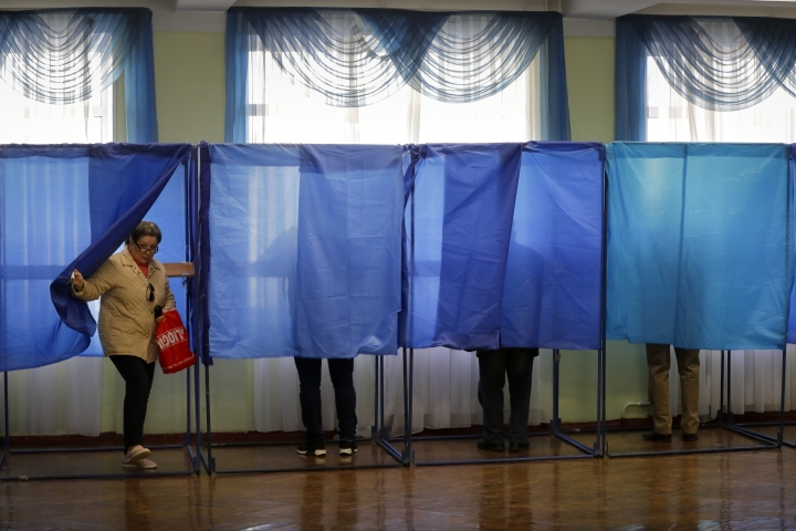 A woman leaves a booth at a polling station, during the second round of presidential elections in Kiev, Ukraine, Sunday, April 21, 2019. Top issues in the election have been corruption, the economy and how to end the conflict with Russia-backed rebels in eastern Ukraine. (AP Photo/Sergei Grits)