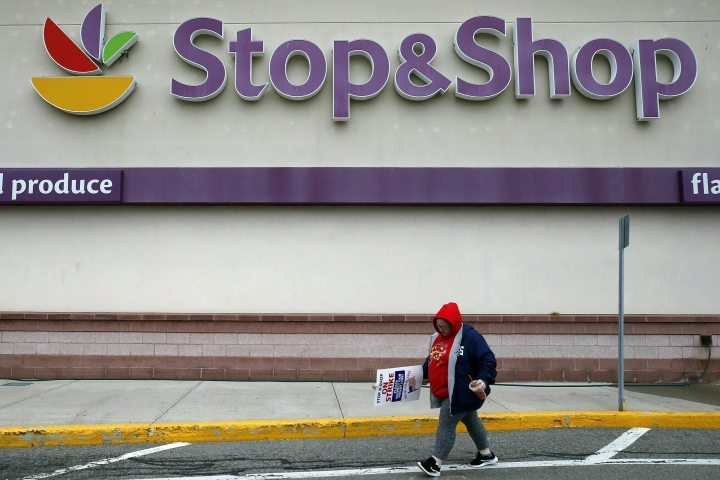 FILE - In this Thursday, April 18, 2019, file photo, a striking worker walks outside a Stop & Shop supermarket in Revere, Mass. Stop & Shop supermarket workers and company officials said Sunday, April 21 they've reached a tentative contract agreement. (AP Photo/Michael Dwyer, File)