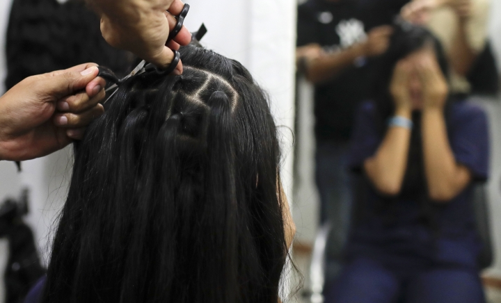 Valery Díaz covers her face as she gets her hair cut off for $100 at a beauty salon in Caracas, Venezuela, Friday, April 5, 2019. Due to lack of water, shampoo and conditioner, Díaz changed her weekly personal hygiene habits and started making and selling bracelets to buy soap and makeup. (AP Photo/Natacha Pisarenko)