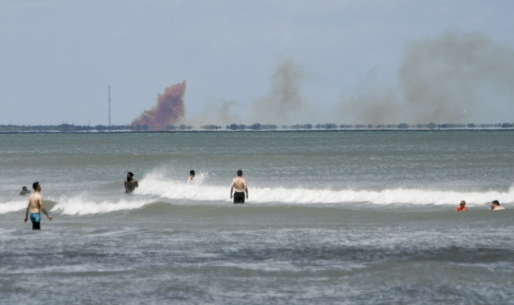 A cloud of orange smoke rises over nearby Cape Canaveral Air Force Station as seen from Cocoa Beach, Fla., Saturday, April 20, 2019. SpaceX reported an anomaly during test firing of their Dragon 2 capsule at their LZ-1 landing site. (Craig Bailey/Florida Today via AP)