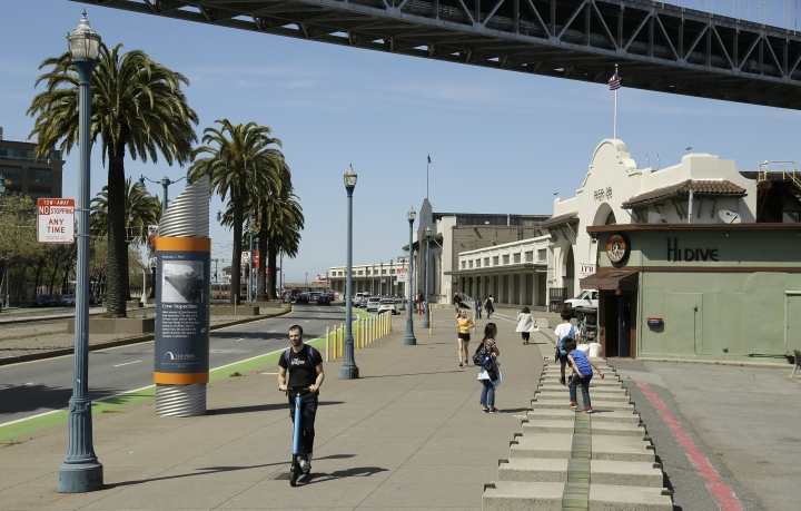 In this photo taken Thursday, April 18, 2019, a man rides a scooter and children play along the Embarcadero across the street from the proposed site of a homeless shelter in San Francisco. The city of San Francisco, which has too little housing and too many homeless people sleeping in the streets, is teeming with anxiety and vitriol these days. A large new homeless shelter is on track to go up along a scenic waterfront area dotted with high-rise luxury condos, prompting outrage from some residents. (AP Photo/Eric Risberg)