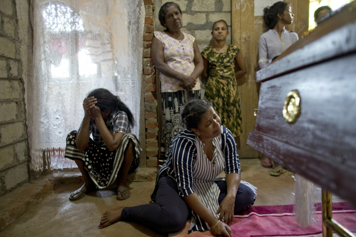 Relatives weep near the coffin with the remains of 12-year Sneha Savindi, who was a victim of Easter Sunday bombing at St. Sebastian Church, after it returned home, Monday, April 22, 2019 in Negombo, Sri Lanka. Easter Sunday bombings of churches, luxury hotels and other sites was Sri Lanka's deadliest violence since a devastating civil war in the South Asian island nation ended a decade ago. (AP Photo/Gemunu Amarasinghe)