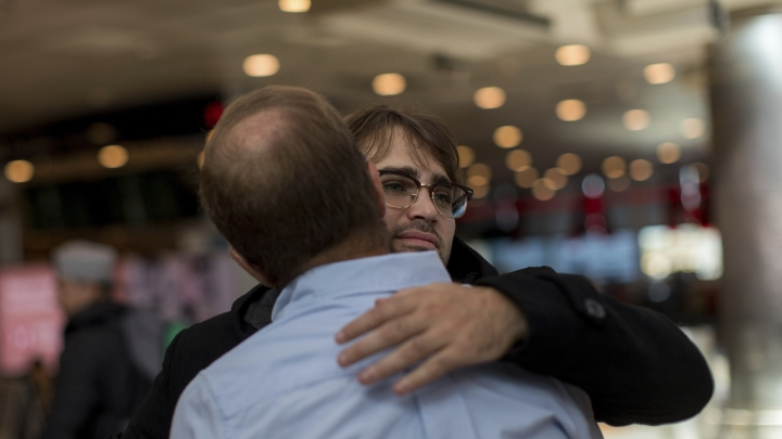 Tomas Ruiz hugs his father Pablo goodbye at the International Airport Ministro Pistarini before boarding a plane to Ireland, in Ezeiza, Argentina, Thursday, April 4, 2019. Tomas' sister recently did the same when she moved to Spain. (AP Photo/Tomas F. Cuesta)