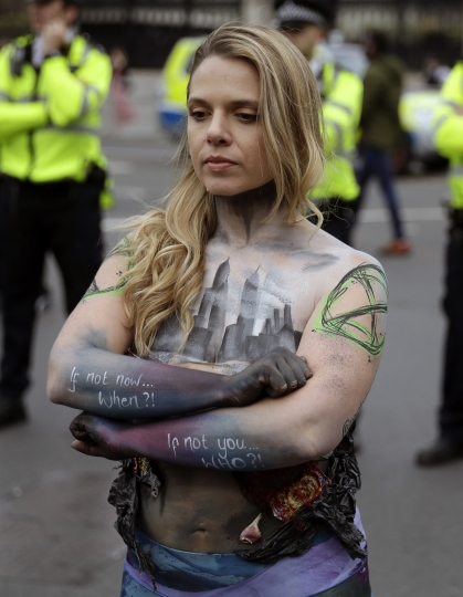 A protester, with half of her body covered in body paint, faces police during a climate protest in Parliament Square, in London, Tuesday April 23, 2019. The non-violent protest group, Extinction Rebellion, is seeking negotiations with the government on its demand to make slowing climate change a top priority. (AP Photo/Matt Dunham)