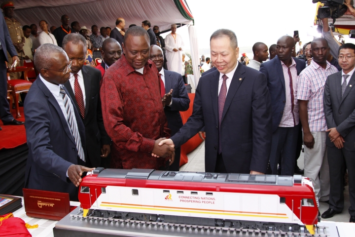 FILE - In this May 30, 2017, file photo, Kenyan President Uhuru Kenyatta, second from left, and Chen Fenjian, president of CCC, shakes hands next to a model of a locomotive during the opening of a Chinese-backed railway costing nearly $3.3 billion, one of the country's largest infrastructure project since independence in Mombasa, Kenya. The railway eventually will link a large part of East Africa to a major port on the Indian Ocean as China seeks to increase trade and influence. Asian and African leaders plan to press Beijing at a conference starting Thursday, April 25, 2019, to reduce the politically volatile debt burden left by its Belt and Road Initiative to build ports and other trade-related infrastructure. (AP Photo/Khalil Senosi, File)
