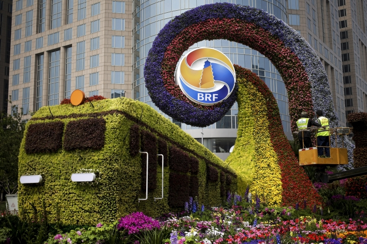 Workers on a platform install flowers on a decoration in a shape of a train for promoting the upcoming Belt and Road Forum in Beijing, Tuesday, April 23, 2019. The Belt and Road Forum which will open by Chinese President Xi Jinping this weekend in the capital city has draw leaders from around the globe. Xi, who has made the initiative a signature policy, agreed last month to seek fairer international trade rules and address the world's economic and security challenges, in what appeared to many as a rebuke to President Donald Trump's protectionist policies. (AP Photo/Andy Wong)