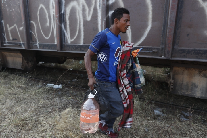 A Central American migrant runs to climb on a passing freight train on his way to the U.S.-Mexico border, in Ixtepec, Oaxaca state, Mexico, Tuesday, April 23, 2019. With throngs of police pickups and small immigration vans parked at checkpoints up and down the narrow waist of southern Mexico, for the migrants hitchhiking, taking buses or walking is no longer an option. (AP Photo/Moises Castillo)