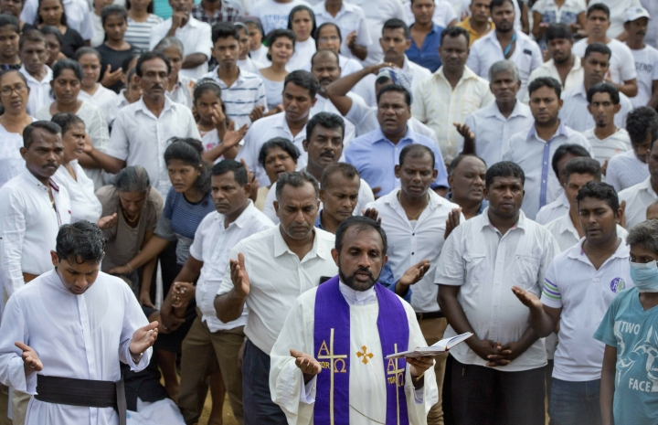 A priest conducts religious rituals during a mass burial for Easter Sunday bomb blast victims in Negombo, Sri Lanka, Wednesday, April 24, 2019. (AP Photo/Gemunu Amarasinghe)