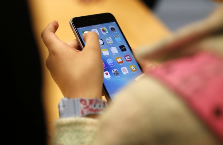 FILE - In this Sept. 25, 2015, file photo, a child holds an Apple iPhone 6S at an Apple store on Chicago's Magnificent Mile in Chicago. The World Health Organization Wednesday, April 24, 2019, issued its first-ever guidance for how much screen time children under 5 should get: not very much, and none at all for those under 1. (AP Photo/Kiichiro Sato, File)