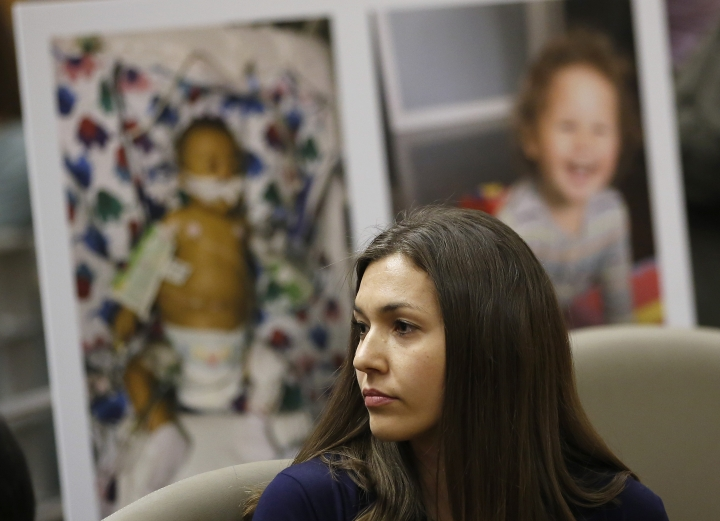 Alyssa Hernandez listens as opponents to a proposal to give state public health officials instead of local doctors the power to decide which children can skip their shots before attending school, speak at the Capitol Wednesday, April 24, 2019, in Sacramento, Calif. Hernandez, whose son Noah, seen in photos in the background, received a liver transplant when he was six months old and cannot be vaccinated against many vaccine-preventable diseases, spoke in support of the bill. (AP Photo/Rich Pedroncelli)