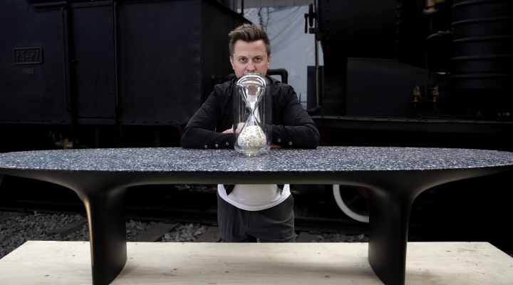 "In this picture taken on Saturday, April 13, 2019, Australian designer Brodie Neill poses next to his creation '""Capsule: Ocean Plastic Hourglass"", on a table made with his self-created Ocean Terrazzo material, made with plastic waste from oceans, at the National Museum of Science and Technology, during the ""RO Plastic - Master's Pieces"" exhibition', on the sidelines of the Salone del Mobile International Furniture Fair week, in Milan, Italy. Scientists and environmental activists have been long raised the alarm on plastic pollution. Now, the high-end design world is getting in on the growing global effort to tackle plastic pollution -- by upcycling discarded objects into desirable one-off design pieces. (AP Photo/Luca Bruno)"