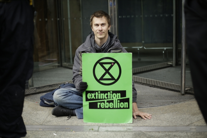 An Extinction Rebellion climate change protester with his hand glued to the floor outside the London Stock Exchange holds a banner in the City of London, Thursday, April 25, 2019. The non-violent protest group, Extinction Rebellion, is seeking negotiations with the government on its demand to make slowing climate change a top priority. (AP Photo/Matt Dunham)