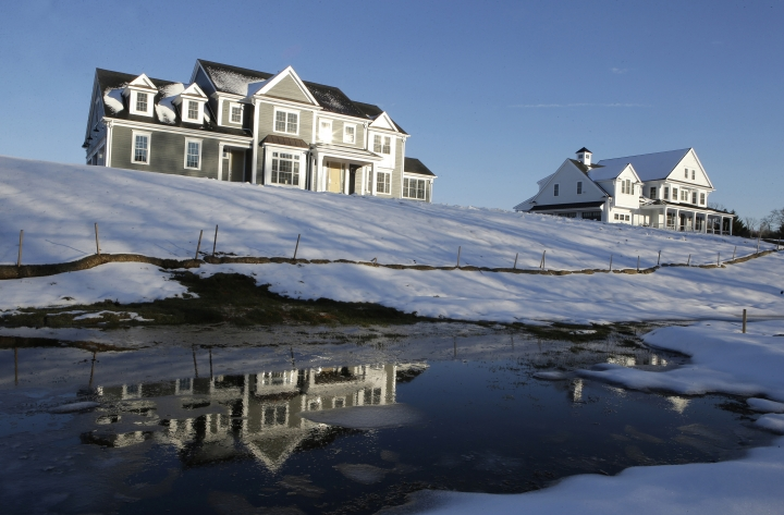 FILE- In this Feb. 21, 2019, file photo a recently constructed home, left, is reflected in water, in Natick, Mass. Before squeezing every last nickel into a down payment on a home mortgage, set some cash aside to handle unexpected expenses after the closing. (AP Photo/Steven Senne, File)