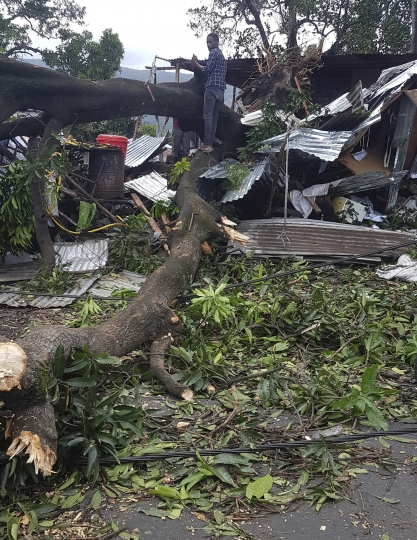 A man stands on fallen trees which damaged his home in Moroni, Comoros, Thursday, April 25, 2019 after Cyclone Kenneth hit the island nation of Comoros. As the powerful tropical cyclone is expected to make landfall by early Friday in northern Mozambique, just six weeks after Cyclone Idai devastated the the central part of the country and left hundreds dead. (AP PhotoAnziza M'Changama)