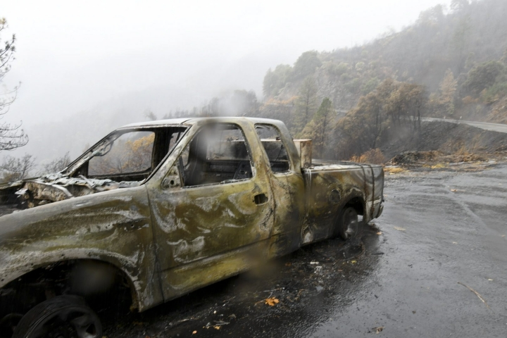 FILE - This Nov. 23, 2018, file photo shows photo shows a burned-out truck in steep terrain along Highway 70 near the boundary of Plumas National Forest. The stretch of highway is in an area the United States Geological Survey considers at high risk for debris flows due to rain soaking terrain burned in the Camp fire. (Benjamin Spillman/The Reno Gazette-Journal via AP)