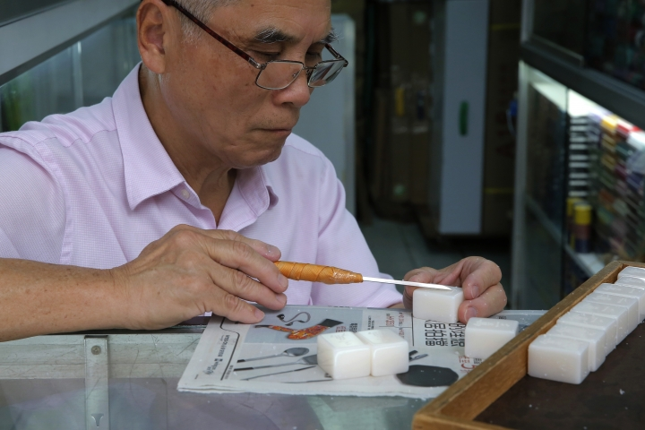 In this April 18, 2019, photo, Cheung Shun-king, 65-year-old maker of the popular table-top game mahjong tiles, engraves a character on a tile in his decades-old store 100 square feet downstairs shop in a Kowloon's old neighborhood of Hong Kong. Hand-carved mahjong tiles is a dying art in Hong Kong. But a small 50-year-old mahjong tile shop is trying to revive the heritage/raise people's interest by organizing hand-craved tile class to keep the tradition alive. (AP Photo/Kin Cheung)