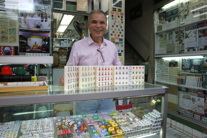 In this April 18, 2019, photo, Cheung Shun-king, 65-year-old mahjong game tiles maker, poses with his mahjong tiles in his decades-old store 100 square feet downstairs shop in a Kowloon's old neighborhood of Hong Kong. Hand-carved mahjong tiles is a dying art in Hong Kong. But Cheung is trying to revive the heritage/raise people's interest by organizing hand-craved tile class to keep the tradition alive. (AP Photo/Kin Cheung)