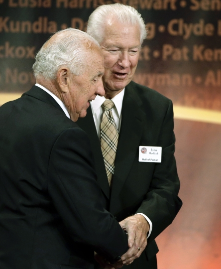 FILE - In this Sept. 8, 2013, file photo, inductee Richie Guerin, left, clasps hands with Hall of Famer John Havlicek, right, after addressing the audience during the enshrinement ceremony for this year's class of the Basketball Hall of Fame, at Symphony Hall in Springfield, Mass. The Celtics said Havlicek died Thursday, April 25, 2019, in Jupiter, Florida. He was 79. (AP Photo/Steven Senne, File)