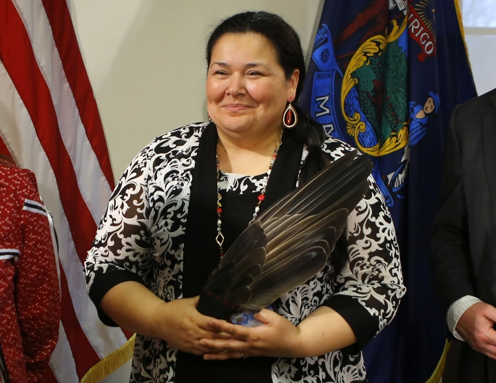 Clarissa Sabattus, Tribal Chief of the Houlton Band of Maliseet Indians, holds eagle feathers during the signing ceremony to establish Indigenous Peoples' Day, Friday, April 26, 2019, at the State House in Augusta, Maine. Gov. Janet Mills signed the bill, adding Maine to the growing number of states who have passed similar legislation. (AP Photo/Robert F. Bukaty)