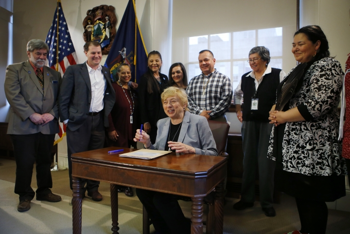 Maine Gov. Janet Mills signs a bill to establish Indigenous Peoples' Day, Friday, April 26, 2019, at the State House in Augusta, Maine. Mills added Maine to the growing number of states changing Columbus Day to Indigenous Peoples' Day. (AP Photo/Robert F. Bukaty)