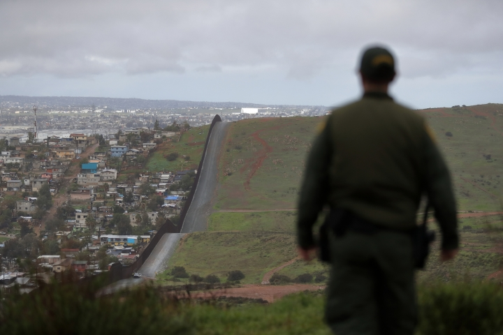 FILE - In this Feb. 5, 2019, file photo, Border Patrol agent Vincent Pirro looks on near a border wall that separates the cities of Tijuana, Mexico, and San Diego, in San Diego. U.S. border authorities say they've started to increase the biometric data they take from children 13 years of age and younger, including fingerprints, despite privacy concerns and government policy intended to restrict what can be collected from migrant youth. (AP Photo/Gregory Bull, File)