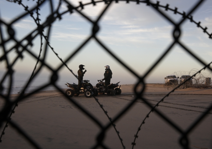 FILE - In this Jan. 9, 2019, file photo, two U.S. Border Patrol agents talk along the beach in San Diego, seen through razor wire lining the border wall from Tijuana, Mexico. U.S. border authorities say they've started to increase the biometric data they take from children 13 years of age and younger, including fingerprints, despite privacy concerns and government policy intended to restrict what can be collected from migrant youth. (AP Photo/Gregory Bull, File)