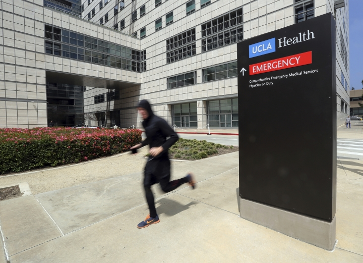 A runner passes the Ronald Reagan UCLA Medical Center on the campus of the University of California, Los Angeles Friday, April 26, 2019. Some students and employees possibly exposed to measles at two Los Angeles universities were still quarantined on campus or told to stay home Friday, but the numbers were dwindling as people were able to show they were vaccinated for the highly contagious disease. The measures were ordered this week at UCLA and California State University, Los Angeles. (AP Photo/Reed Saxon)